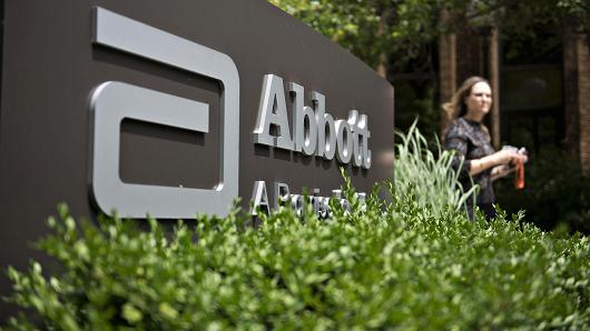 An employee walks near an Abbott Laboratories sign at the company's headquarters complex in Abbott Park, Illinois.