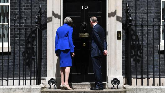 Britain's Prime Minister and leader of the Conservative Party Theresa May (L), accompanied by her husband Philip (R), leaves after delivering a statement outside 10 Downing Street in central London on June 9, 2017