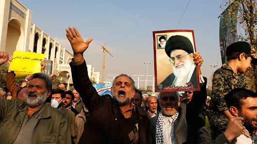 Pro-government demonstrators hold a poster of Iran's supreme leader Ayatollah Ali Khamenei during a march following the weekly Muslim Friday prayers in Tehran on January 5, 2018.
