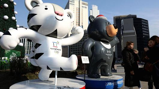 People walk in front of mascots of the 2018 PyeongChang Winter Olympic and Paralympic Games Soohorang (L) and Bandabi (R) on January 5, 2018 in Seoul, South Korea.