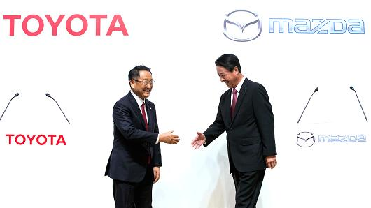 Toyota Motor Co. President Akio Toyoda, left, and Mazda Motor Co. President and CEO Masamichi Kogai, right, shake hands during a photo session at a joint press conference on August 4, 2017 in Tokyo, Japan.