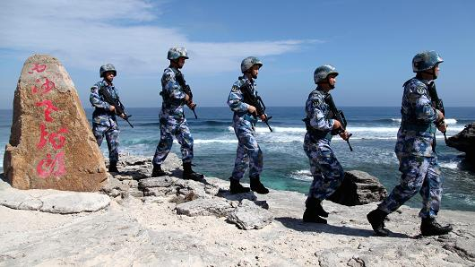 """Soldiers of China's People's Liberation Army (PLA) Navy patrol at Woody Island, in the Paracel Archipelago, which is known in China as the Xisha Islands, January 29, 2016. The words on the rock read, """"Xisha Old Dragon"""". Old Dragon is the local name of a pile of rocks near Woody Island."""